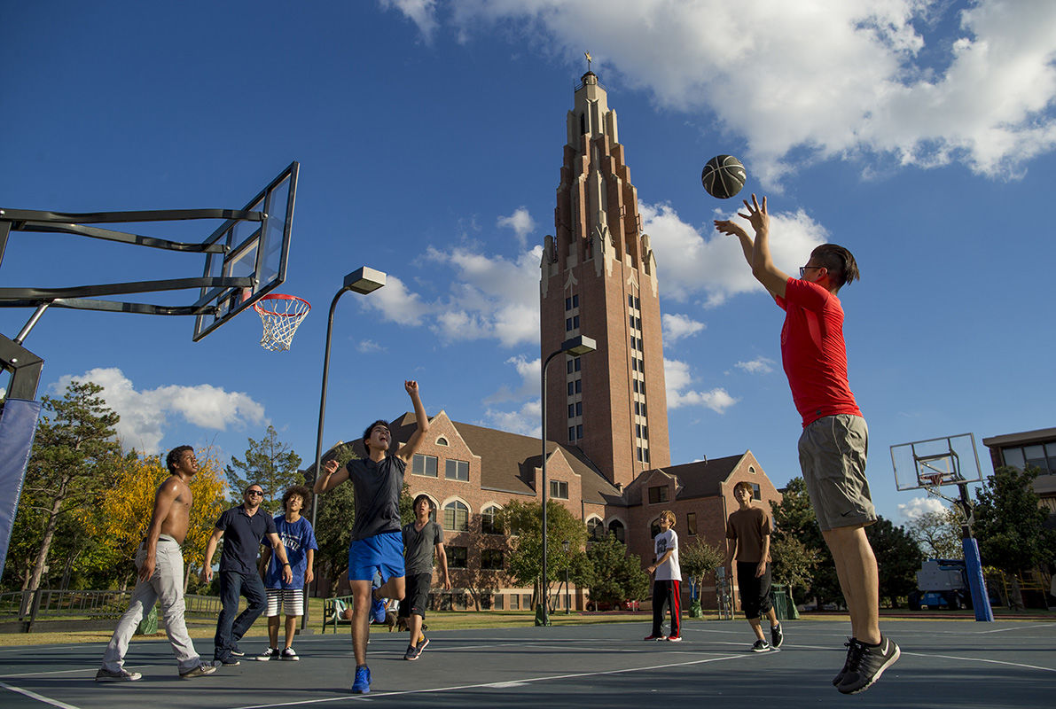 Male students play basketball on a court in front of OCU's Gold Star building.