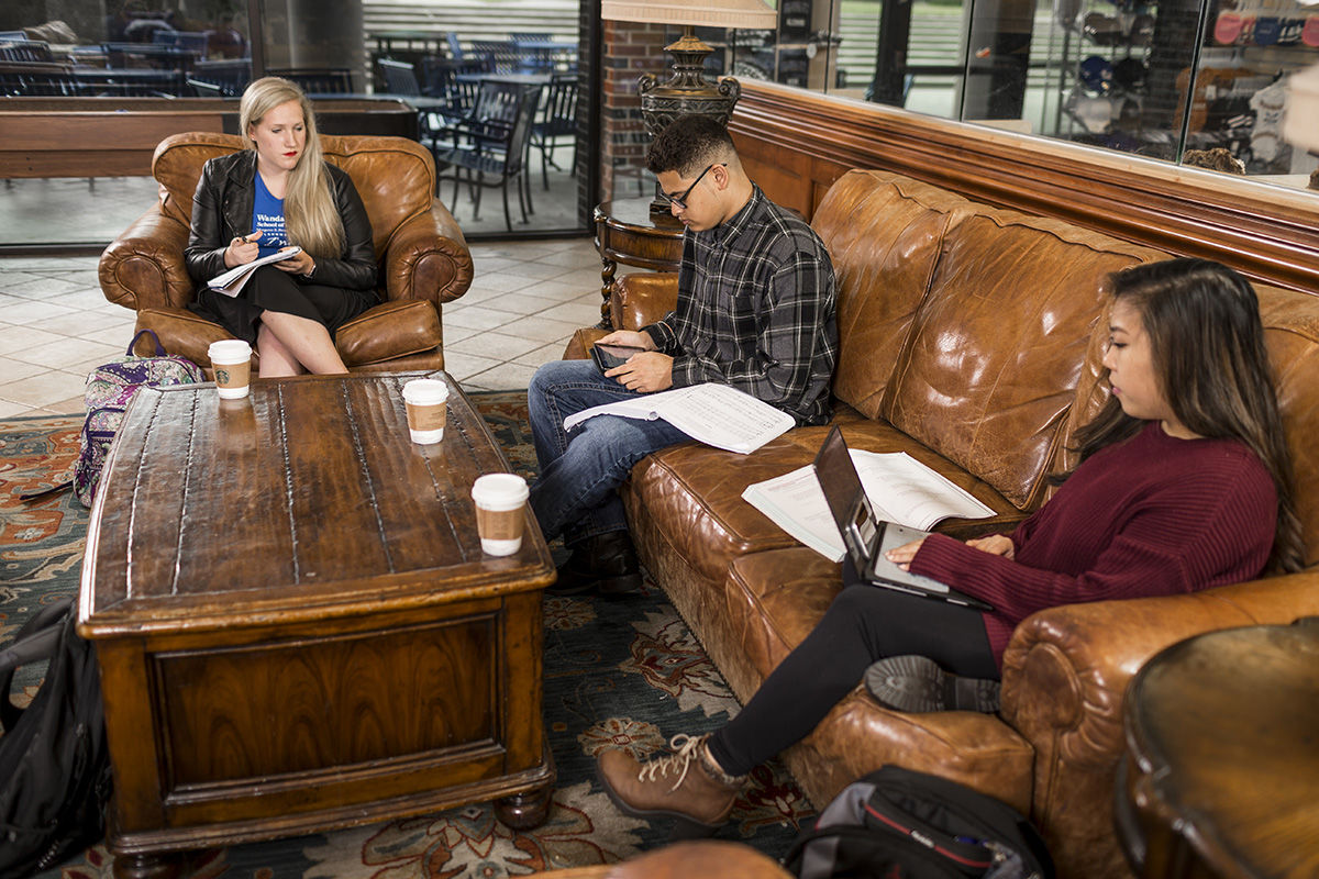 Students sit on a leather sofa and overstuffed chair in a campus lounge.