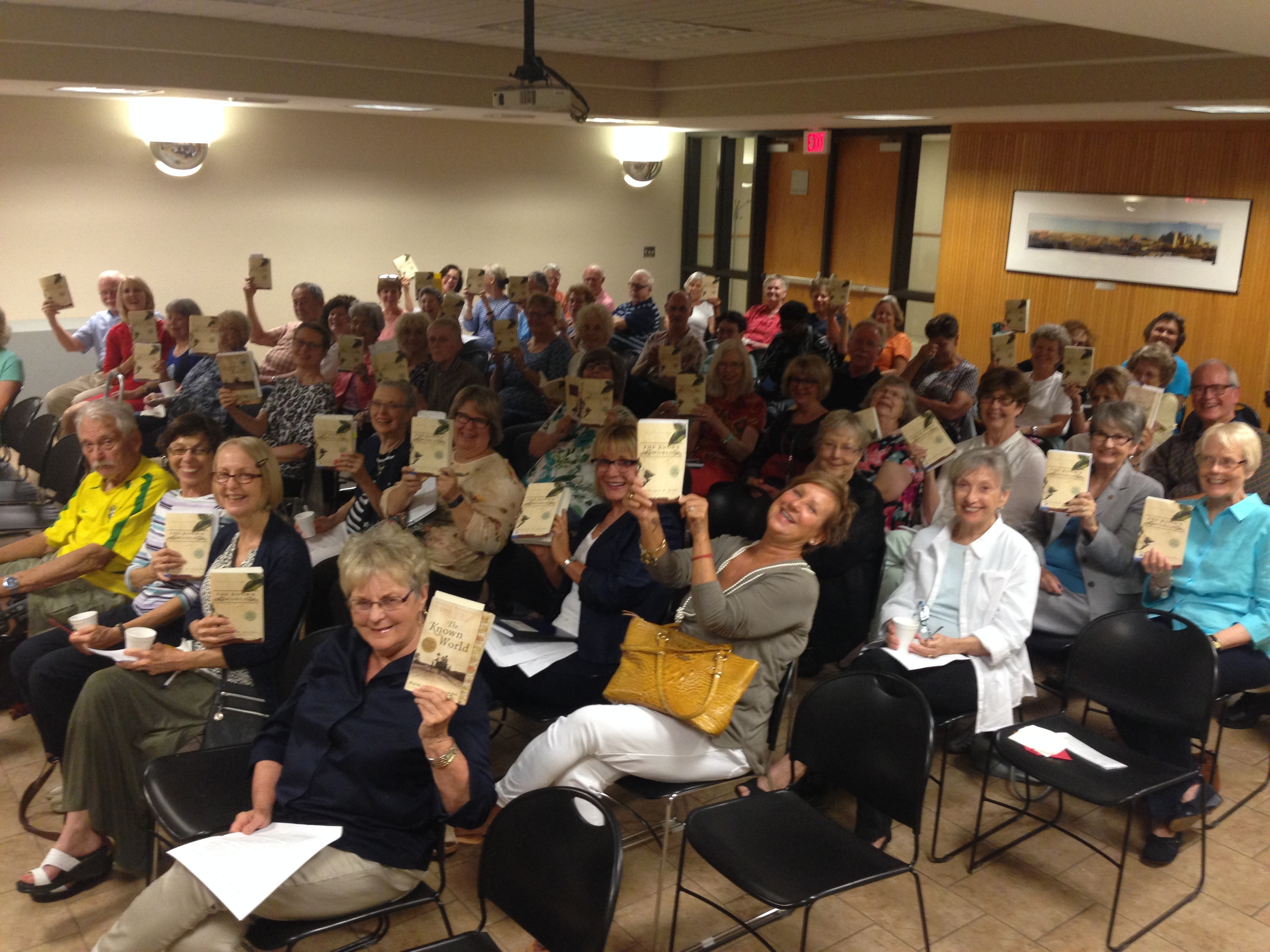 """a room full of """"Let's Talk about it"""" participants holds their books in the air"""