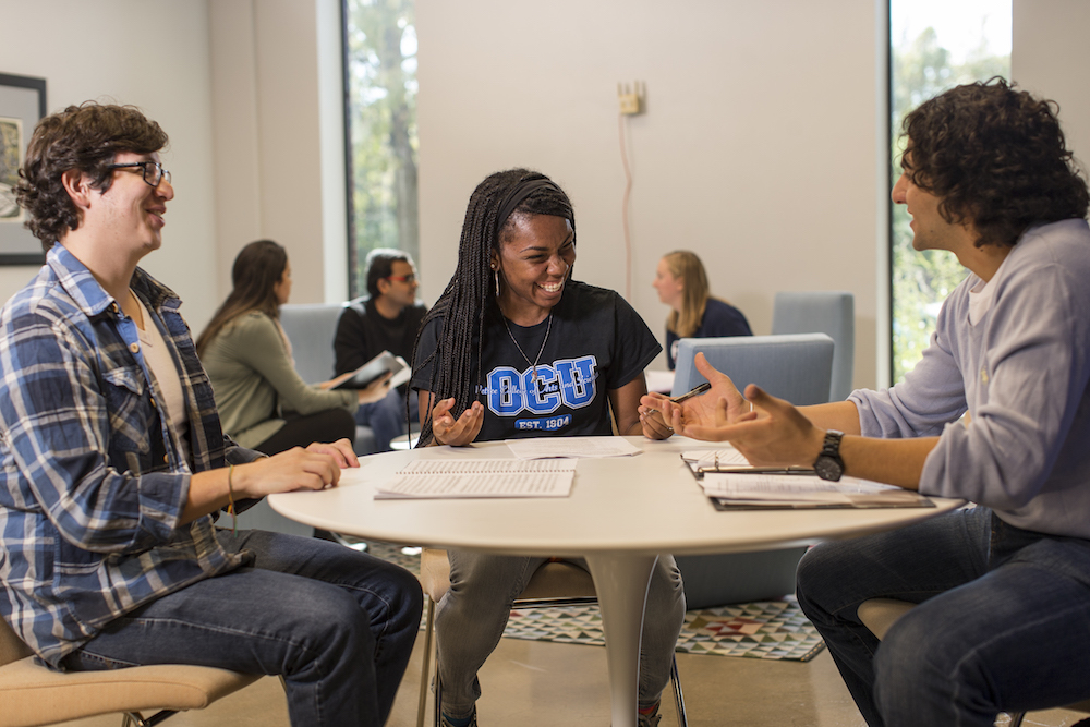 Three students study around a table in a common area.