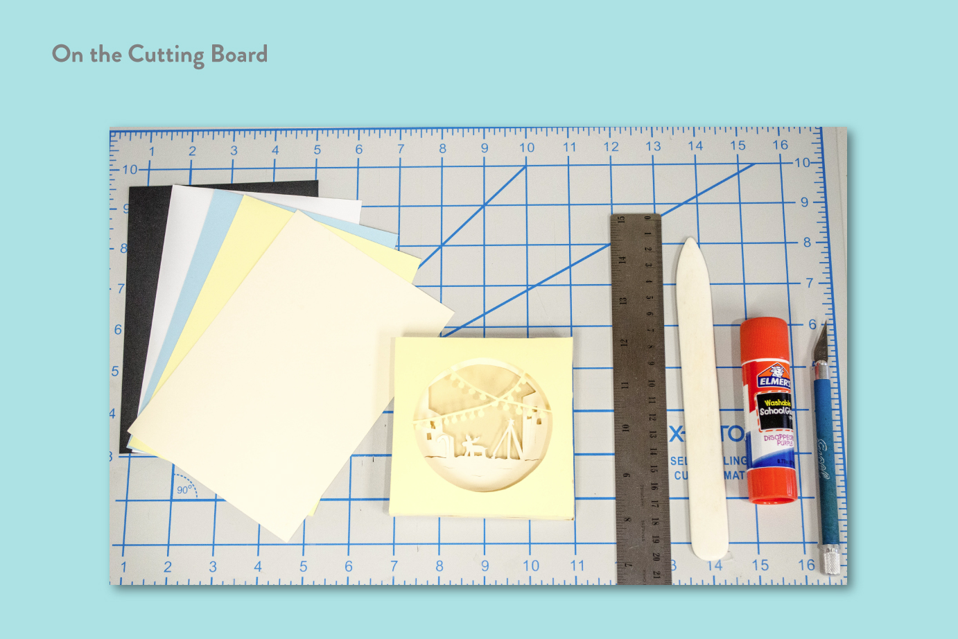 On the Cutting Board (Photo of paper, ruler, glue, and materials to make image for social media use)