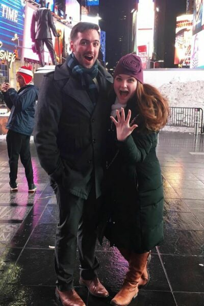 Zack Travers and Virginia Newsome-Travers in Times Square, Virginia is holding up her hand to display her engagement ring