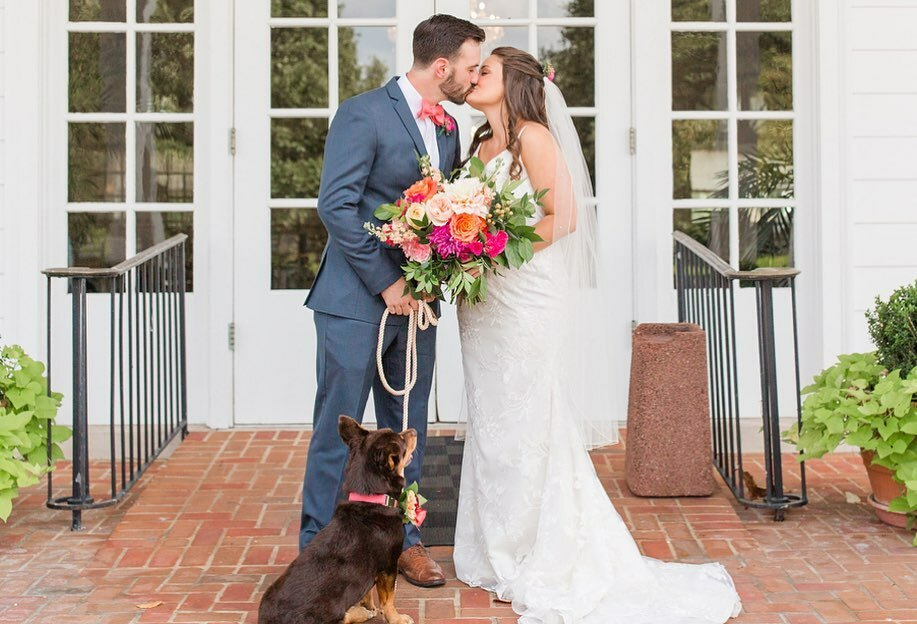 Zack Travers and Virginia Newsome-Travers kissing on their wedding day with their dog standing by their feet