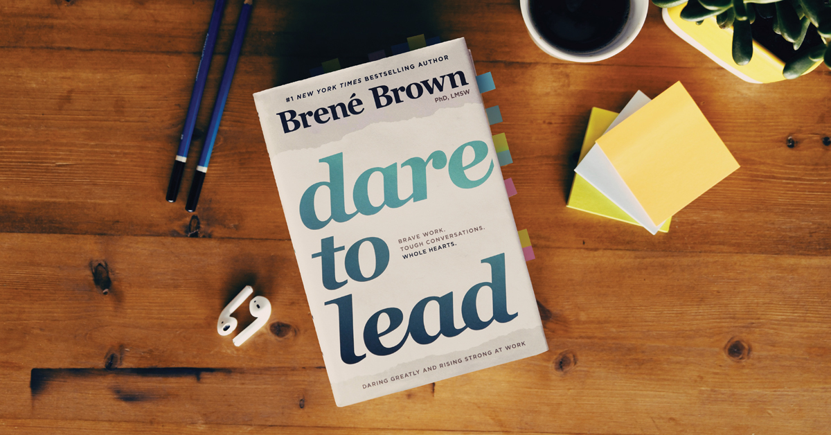 Dare to Lead book by Brene Brown on a table with pencils and a mug of coffee