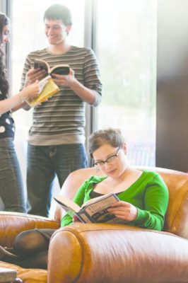 An OKCU student reads in a comfortable chair in the Student Center lobby.