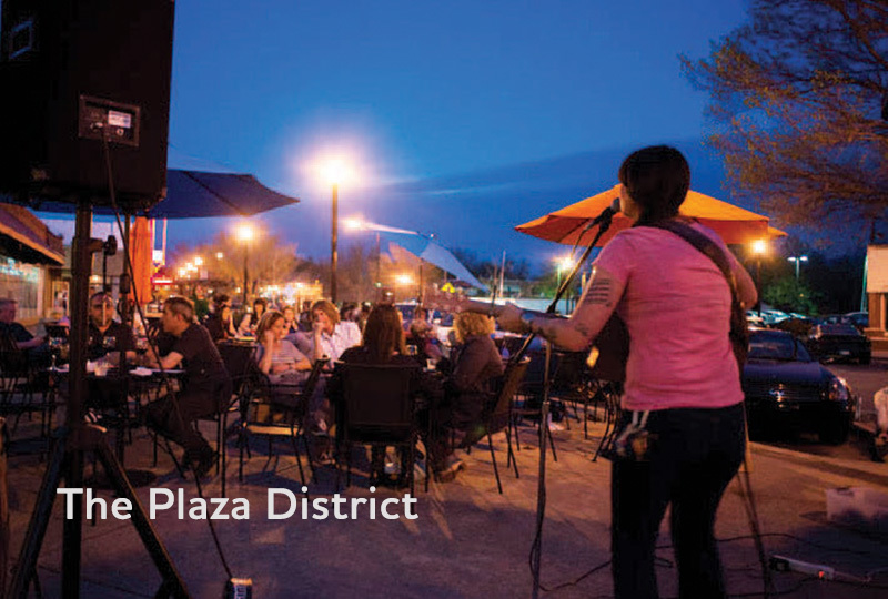 A singer with a guitar performs outdoors in Oklahoma City's Plaza District.