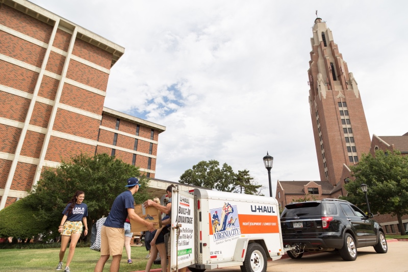 Students unload a trailer as they move in to walker hall on O C U campus