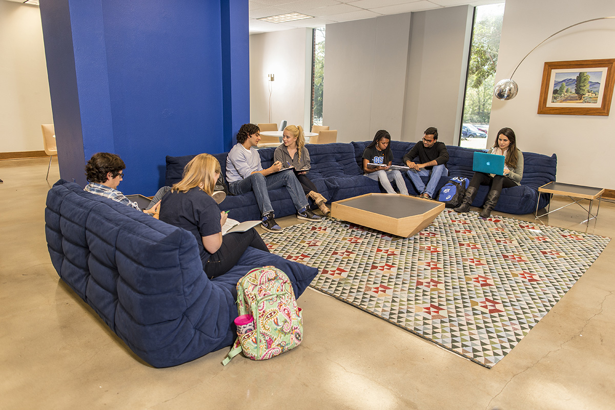 Students sit on a blue U-shaped sofa in the lobby of OKCU's Walker Hall dormitory.