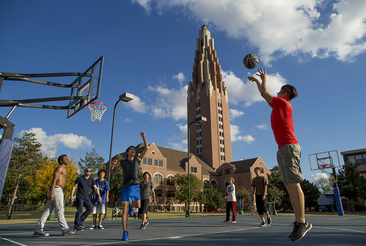Male students play basketball on a court in front of OKCU's Gold Star building.