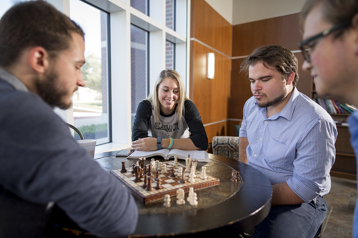 Students face off at a chess board.