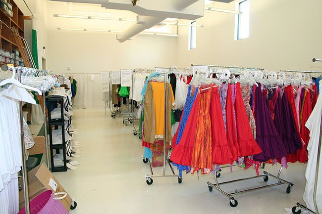 Brightly colored costumes hang on racks in the Lacy Center's costume lab.