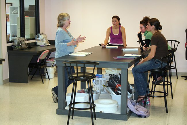 Students listen to an instructor in the Lacy Center's costume lab.