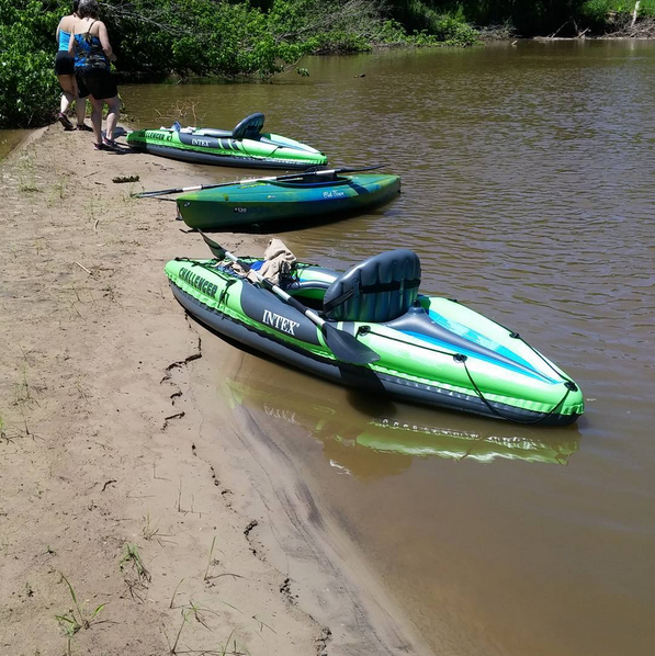 Kayaks sit by a river.