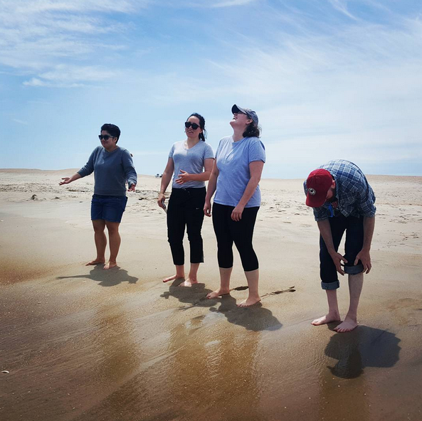 Four people stand on a beach.
