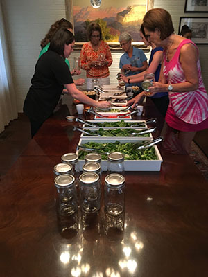 Staff members going through a salad bar line to build their mason jar salads.