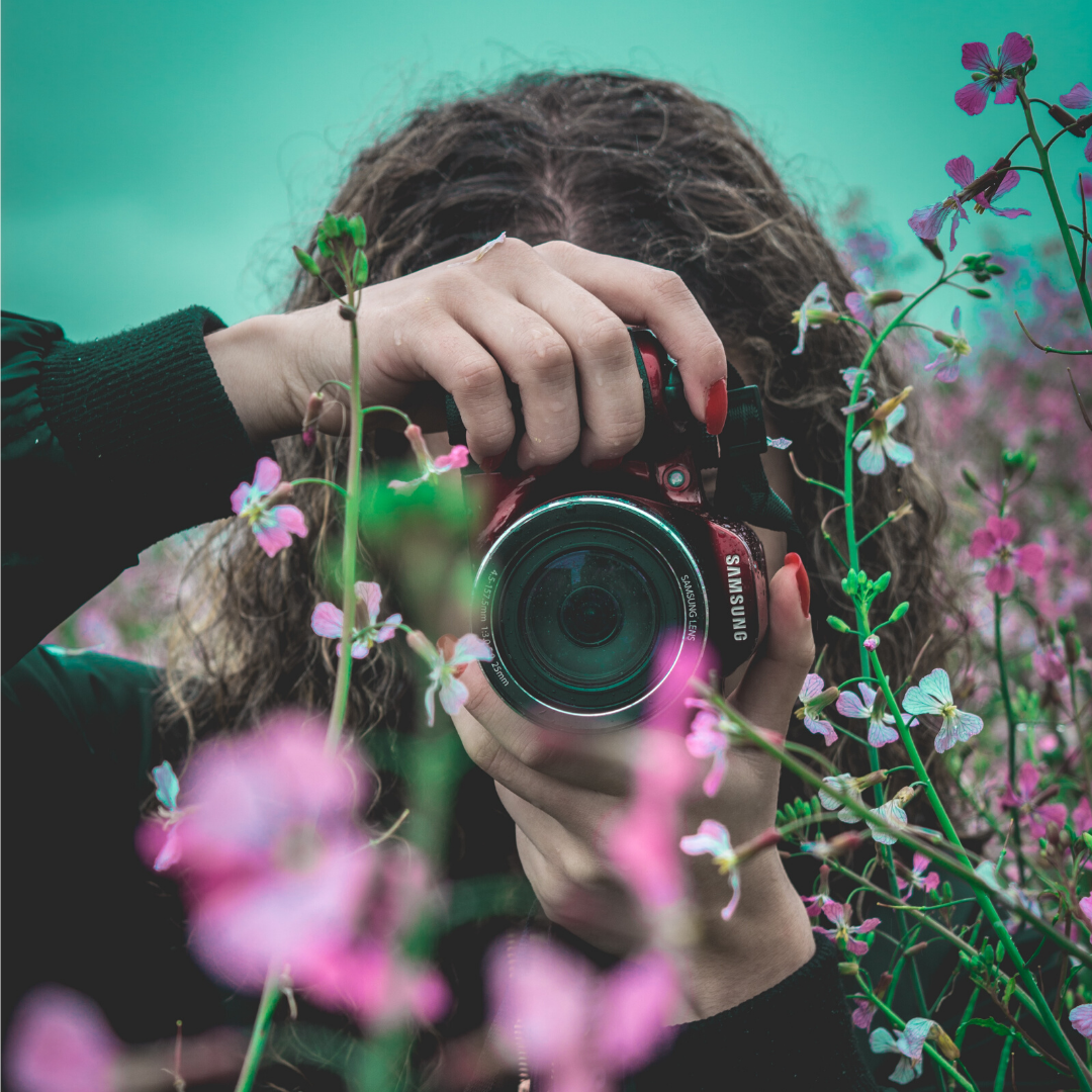 Girl taking photo of flowers