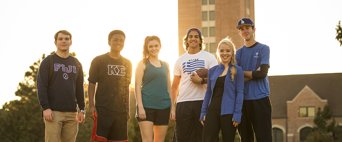 Six Oklahoma City University students stand in front of the Gold Star tower as the sun sets behind them.