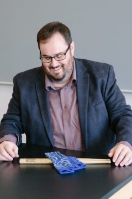 A man in a suit jacket and button-up shirt smiles at a pair of drumsticks.