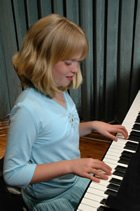 A young girl plays a piano.