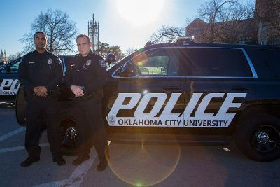 Two OKCU Police officers stand in front of a police SUV.