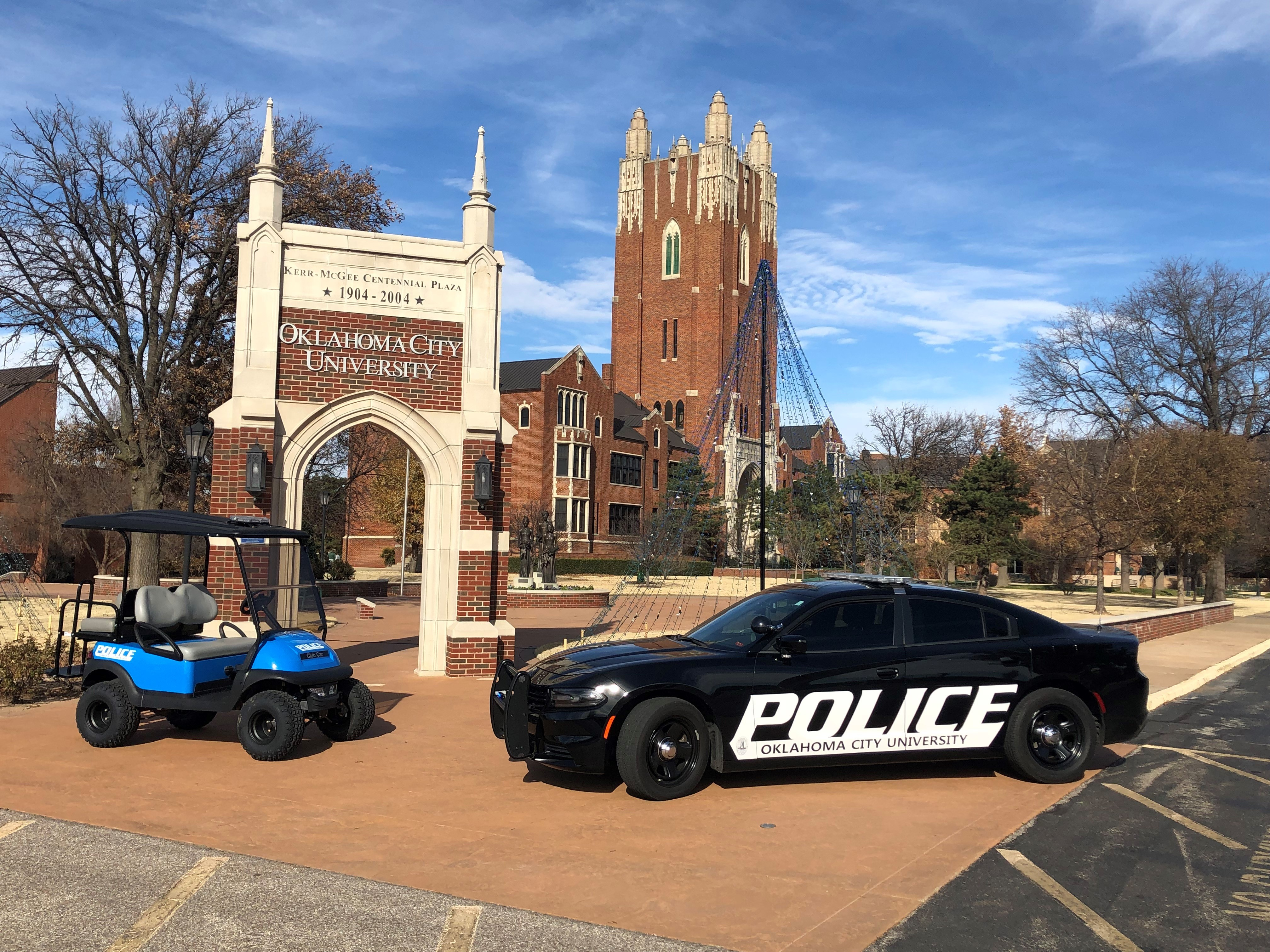 O C U P D vehicles are parked by the campus's entryway