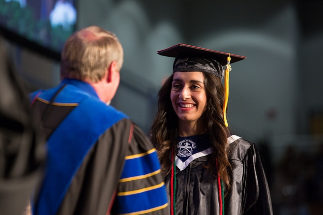 Daniela Galindo shaking Provost Kent Buchanan's hand during commencement