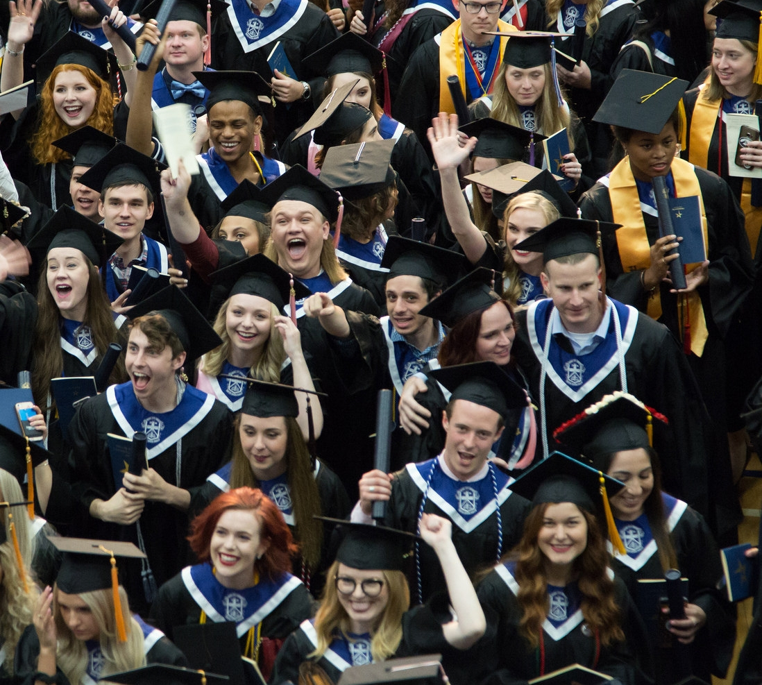 Graduates cheering after commencement ceremony