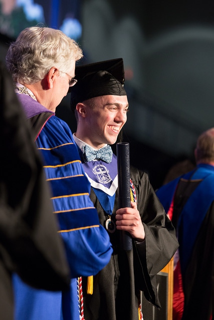 Matthew Sparks receiving diploma from President Robert Henry during commencement