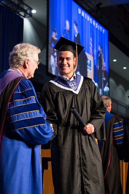 Vladimir Kalajdzic and President Robert Henry shaking hands during commencement ceremony